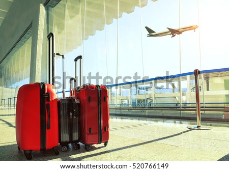stack of traveling luggage in airport terminal and passenger plane flying over sky Royalty-Free Stock Photo #520766149