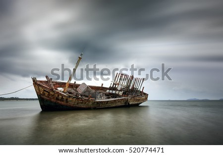 An old shipwreck boat abandoned stand on beach or Shipwrecked off the coast of Thailand. #520774471