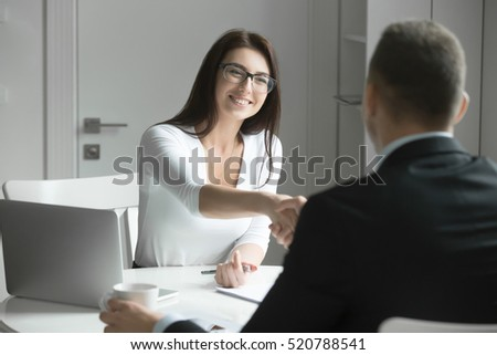 Friendly smiling businessman and businesswoman handshaking over the office desk after pleasant talk and effective negotiation, good relationships. Business concept photo Royalty-Free Stock Photo #520788541