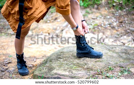 Woman hiking tying shoelace on forest trail, soft and select focus #520799602