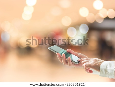 Digital lifestyle business person or shopper using mobile smart phone for retail shopping in mall
