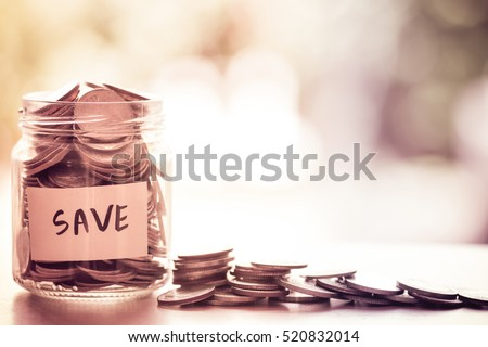 Coins in glass jar for money saving financial concept Royalty-Free Stock Photo #520832014