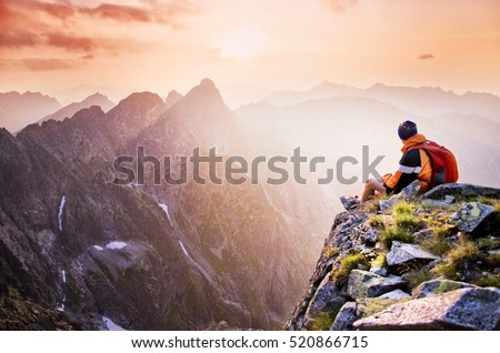 Young male hiker with backpack relaxing on top of a mountain during calm summer sunset - scenery from vacation - photo with space for your montage. #520866715