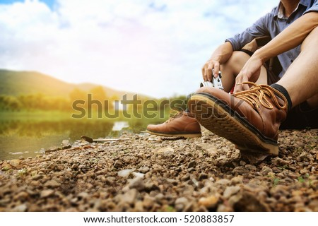 Traveler sitting on the ground at a river for take a photo with copy space. Travel concept.