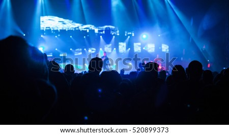 Crowd at concert - Cheering crowd in front of bright colorful stage lights #520899373