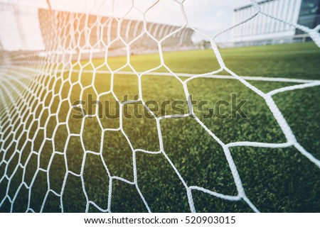 Soccer or football net background, view from behind the goal with blurred stadium and field pitch. #520903015