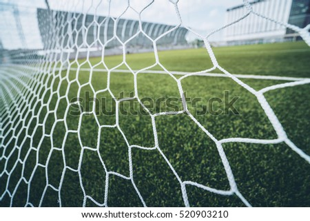 Soccer or football net background, view from behind the goal with blurred stadium and field pitch. #520903210