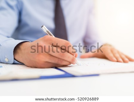 Businessman writing in a document. Focus on the tip of the pen #520926889