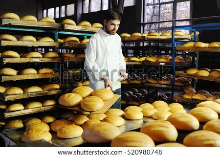Young handsome guy with a baker baking shovel gets hot bread from the oven in the background bread factory #520980748