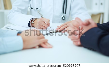 Female medicine doctor hand holding silver pen writing something on clipboard closeup. Ward round, patient visit check, medical calculation and statistics concept. Physician ready to examine patient #520998907