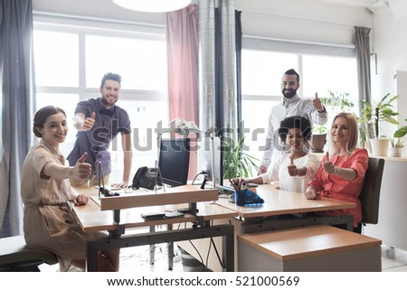 business, startup and people concept - happy creative team showing thumbs up in office #521000569