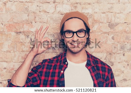 Portrait of cheerful hipster man in glasses gesturing ok Royalty-Free Stock Photo #521120821