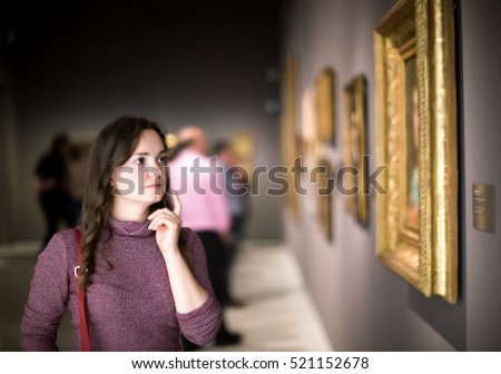 Portrait of positive young girl attentively looking at paintings in art museum  Royalty-Free Stock Photo #521152678