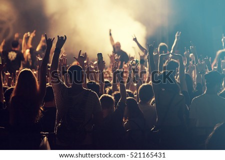 Crowd at concert - Cheering crowd in front of bright colorful stage lights Royalty-Free Stock Photo #521165431