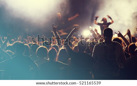 Crowd at concert - Cheering crowd in front of bright colorful stage lights Royalty-Free Stock Photo #521165539