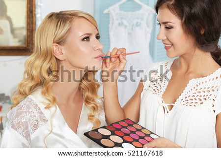 Professional makeup artist applying lip gloss #521167618