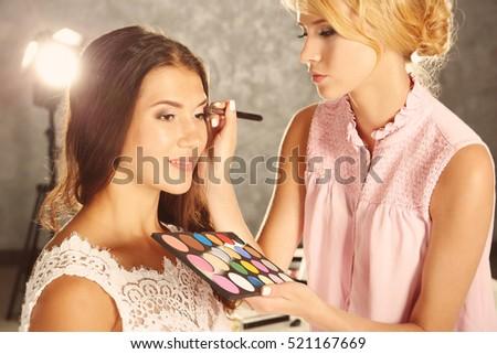 Wedding preparation. Professional makeup artist applying eye shadow to bride #521167669