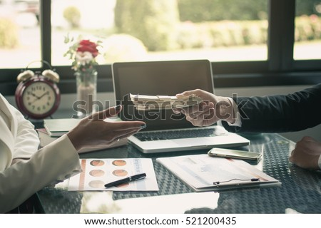 Man offering batch of hundred dollar bills. Hands close up. Venality, bribe, corruption concept. Hand giving money - United States Dollars (or USD). Hand receiving money from businessman. #521200435