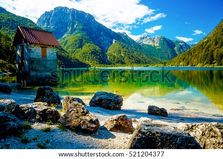 small building at a beautiful lake surrounded by stunning mountain landscape #521204377
