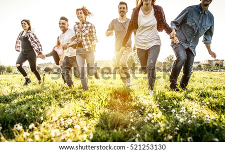 Group of friends running happily together in the grass #521253130