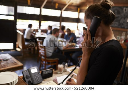 Young woman taking a reservation by phone at a restaurant Royalty-Free Stock Photo #521260084