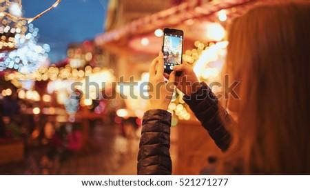 Woman Taking Pictures of European Christmas Market Scene on Smartphone. 4K. Girl Enjoying Winter Holiday Season, visiting Outdoors Christmas Market, Making photos on cell phone. Travel Europe