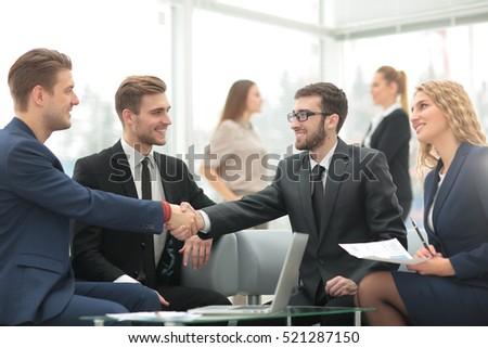 Handshake between businesspeople in a modern office #521287150
