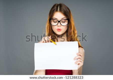 Surprised young business female worker in glasses showing blank  over gray background isolated, holding white A4 paper poster, showing something with pen, using pen #521288323