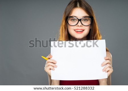 Relaxed Smiling young business female worker in glasses showing blank  over gray background isolated, holding white A4 paper poster, showing something with pen, using pen #521288332