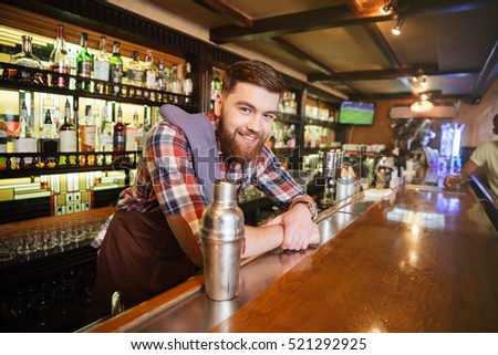Portrait of cheerful young bartender standing and smiling in bar  #521292925