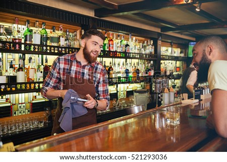 Smiling attractive young barman wiping glasses and talking to african american young man in bar #521293036