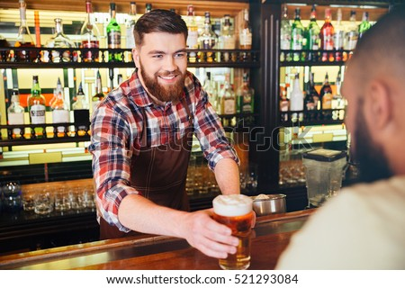 Cheeful attractive bearded young bartender giving glass of beer to customer in bar #521293084