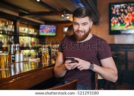Happy handsome young man sitting and using mobile phone in pub #521293180