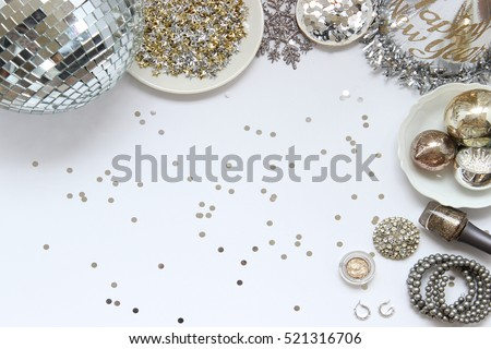 Over head flat lay New Years Eve party decorations and beauty/fashion products. Disco ball, star confetti, snowflake, glitter, party hat, makeup, jewelry and ornaments. Frame with room for copy. #521316706