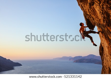 Rock climber resting while climbing overhanging cliff Royalty-Free Stock Photo #521331142
