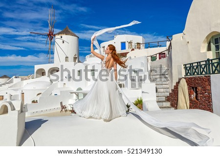 Beautiful woman with red hair in white dress on background of the architecture in Santorini #521349130
