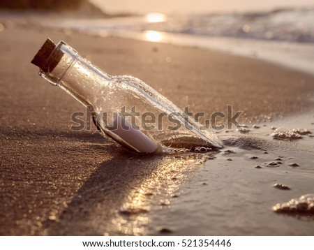 Message in the bottle washed ashore against the Sun setting down Royalty-Free Stock Photo #521354446