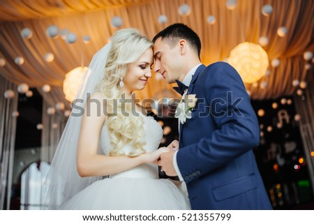 Wedding. Happy bride and elegant groom holding hands while standing next to each other in luxury apatment. Wedding day. #521355799