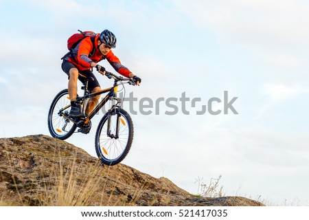 Cyclist in Red Jacket Riding the Bike Down Rocky Hill. Extreme Sport Concept. #521417035