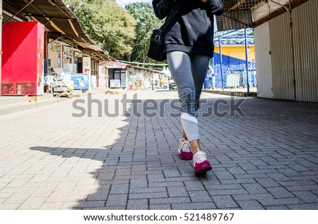 Feet girl walking down the street in sweat pants and sneakers. Shadow on the market #521489767