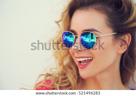 Close Up Portrait of Happy Fashion Woman in Sunglasses. Smiling Trendy Girl in Summer. Laughing Female. White Wall Background Copy Space. Not Isolated Toned Photo. Royalty-Free Stock Photo #521496283