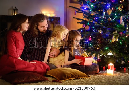 Young happy family of four unwrapping Christmas gifts by a fireplace in a cozy dark living room on Christmas eve #521500960