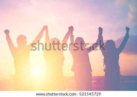 Silhouette of happy business team making high hands in city background for business teamwork concept