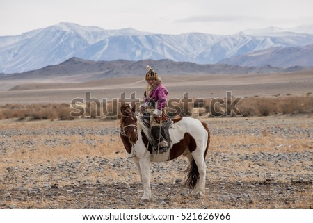 Beautiful Mongolian girl traditionally wearing typical Mongolian Fox dress culture of Mongolia she Rider horse in Altai Mountain background  at Ba-yan UlGII, MONGOLIA #521626966