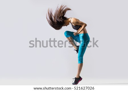 One cool beautiful young fit modern dancer lady in blue sportswear warming up, working out, dancing with her long hair flying, full length, studio image on gray background #521627026