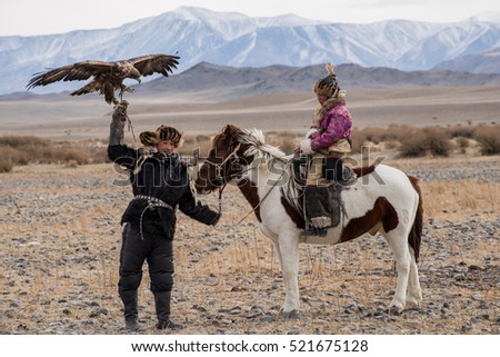 Kazakh Eagle Hunters in traditionally wearing typical Mongolian dress culture of Mongolia she Rider horse on Altai Mountain background  at Ba-yan UlGII, MONGOLIA #521675128