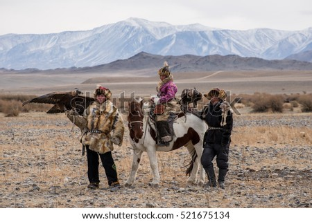Kazakh Eagle Hunters in traditionally wearing typical Mongolian dress culture of Mongolia she Rider horse on Altai Mountain background  at Ba-yan UlGII, MONGOLIA #521675134