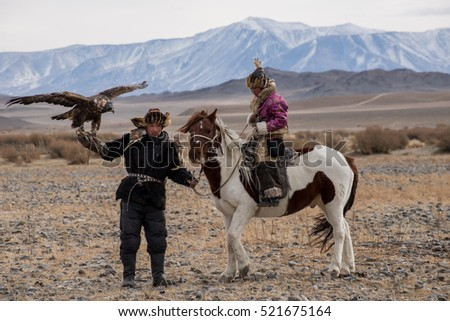 Kazakh Eagle Hunters in traditionally wearing typical Mongolian dress culture of Mongolia she Rider horse on Altai Mountain background  at Ba-yan UlGII, MONGOLIA #521675164