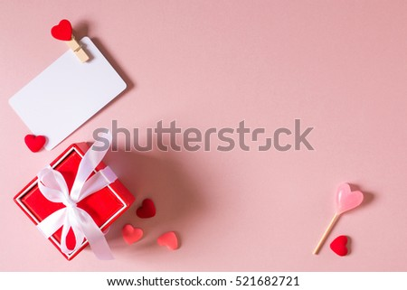 Valentine day composition: red gift box with bow, credit / visiting card template with clamp, candy and small hearts on light pink background. Top view. #521682721