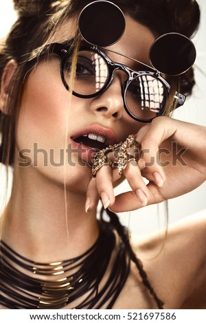 Beautiful fashion woman with creative make-up and hairstyle wearing glasses and jewelry. The beauty of the face. Photos shot in the studio.